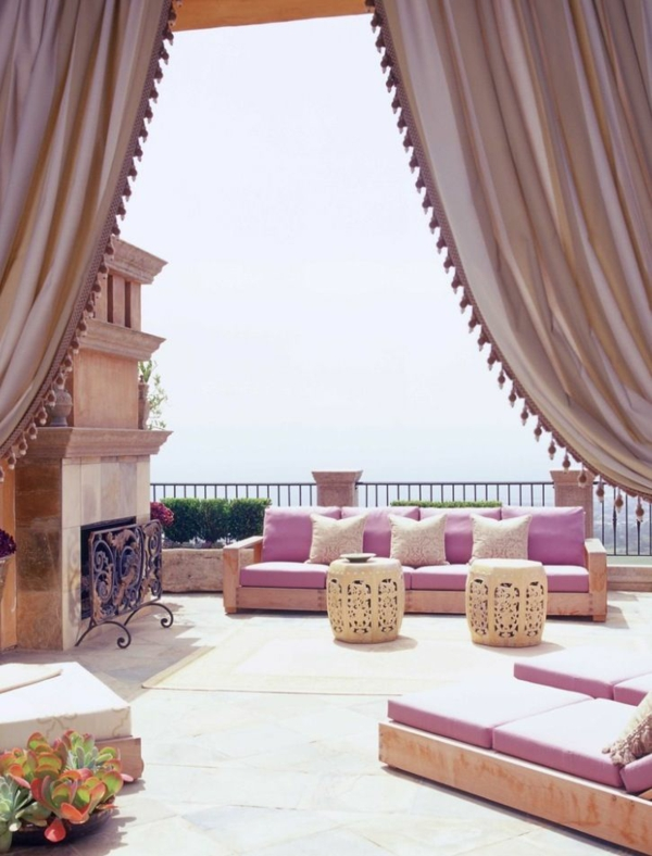 Roof terrace design in oriental style outdoor fireplace sofa lounger curtains canopy